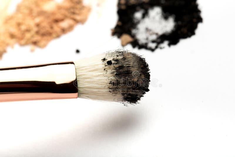 Close-up zijaanzicht van professionele samenstellingsborstel met natuurlijk varkenshaar en zwarte metalen kap met verpletterde di royalty-vrije stock fotografie