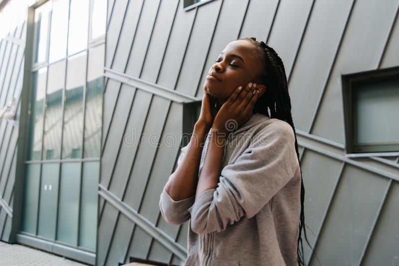 Close-up zijportret van het vrij Afro-Amerikaanse meisje die van de muziek in de oortelefoons genieten stock fotografie