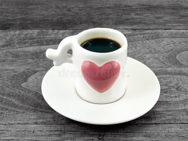 Close-up zwarte koffie in kleine witte koffiekop met groot roze hart op witte schotel en donkere houten lijstvloer stock foto