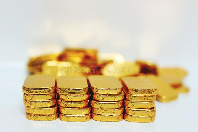 Close-upbeeld die van vele goudstaven zich op wat gouden Gouden Witte achtergrond punten Gouden van de bedrijfsmarionettenbespari royalty-vrije stock foto