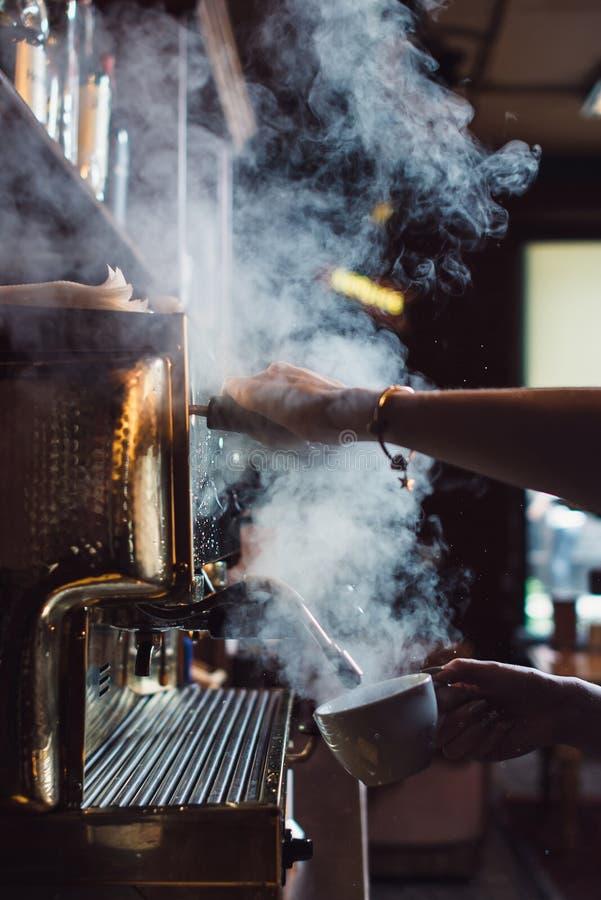 Close-upbeeld die van vrouwelijke barista koffie-makende machine met behulp van aan stoommelk in koffie stock fotografie