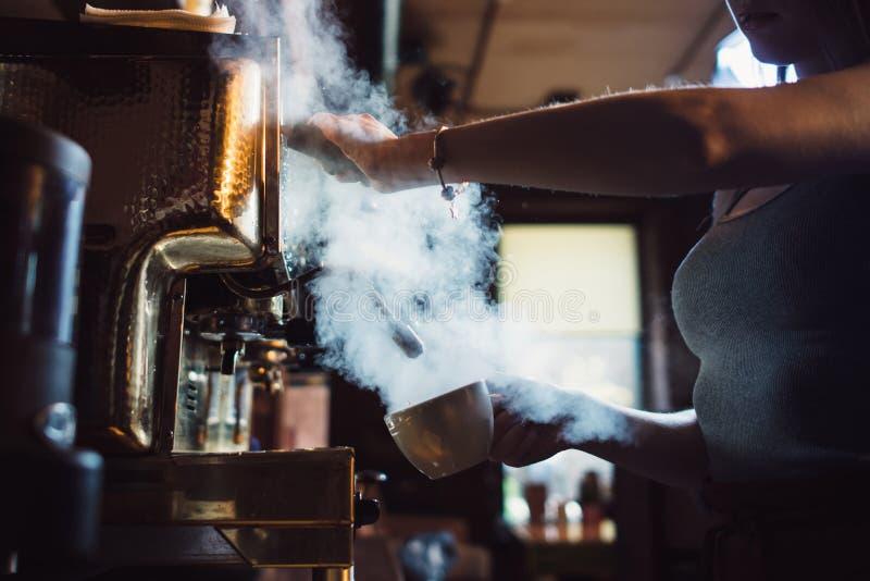 Close-upbeeld die van vrouwelijke barista koffie-makende machine met behulp van aan stoommelk in koffie royalty-vrije stock foto's