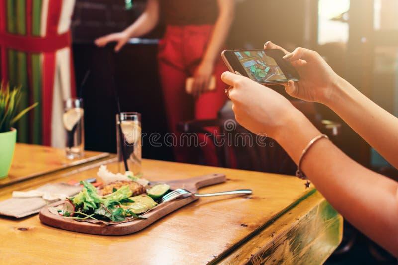 Close-upbeeld die van vrouwelijke handen een mobiele telefoon houden die beeld van gezonde heerlijke schotel in koffie nemen stock foto