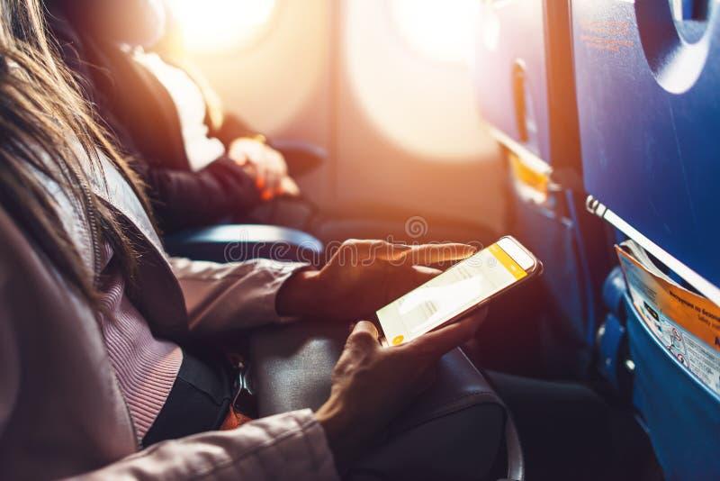 Close-upbeeld die van vrouwelijke handen smartphonezitting in het vliegtuig houden royalty-vrije stock foto's