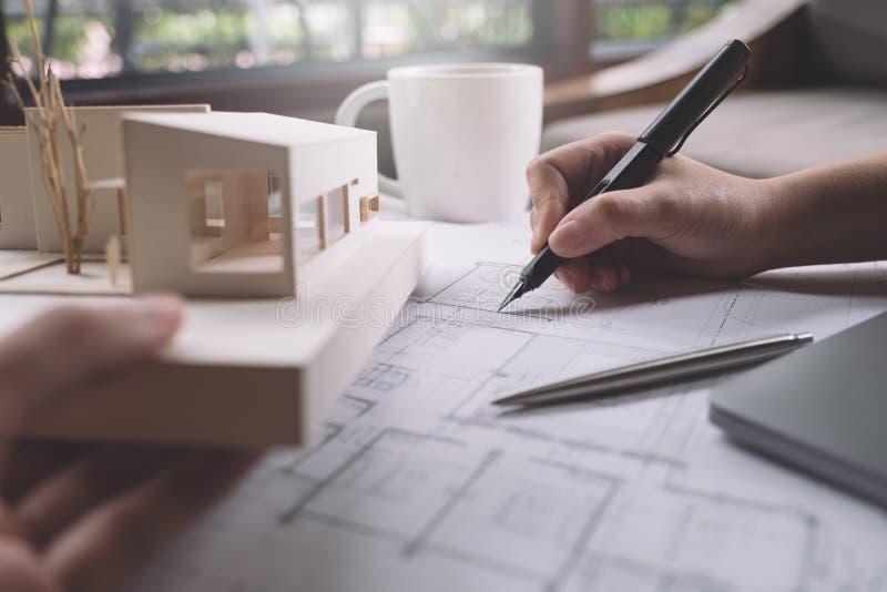 Close-upbeeld van architecten die het document van de winkeltekening met architectuurmodel trekken royalty-vrije stock afbeelding