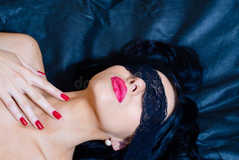 Close-upbeeld van blinddoek jonge mooie sexy donkerbruine vrouw met rode die lippenstift, spijkersogen in kantband worden behande stock foto's