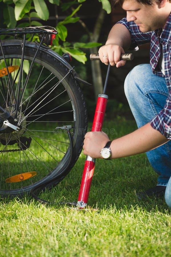 Close-upbeeld van de jonge mens die luchtpomp gebruiken om vlakke fietsband te bevestigen stock foto