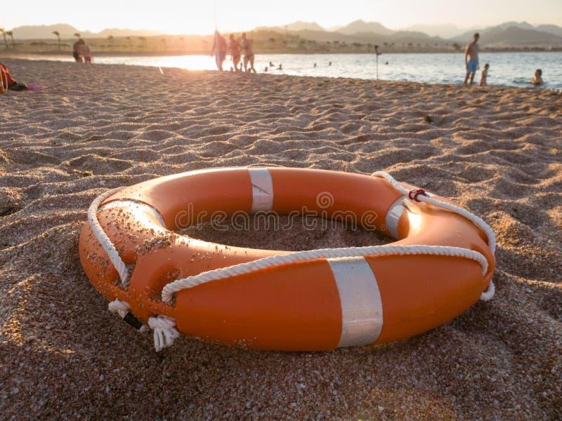Close-upbeeld van de rode plastic ring van de het levensbesparing op zandig overzees strand bij zonsonderganglicht royalty-vrije stock foto