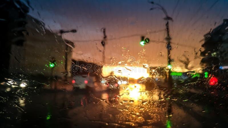 Close-upbeeld van druppeltjes op nat autowindscherm in regen bij zonsonderganglicht De samenvatting schoot van natte voorruit een stock foto