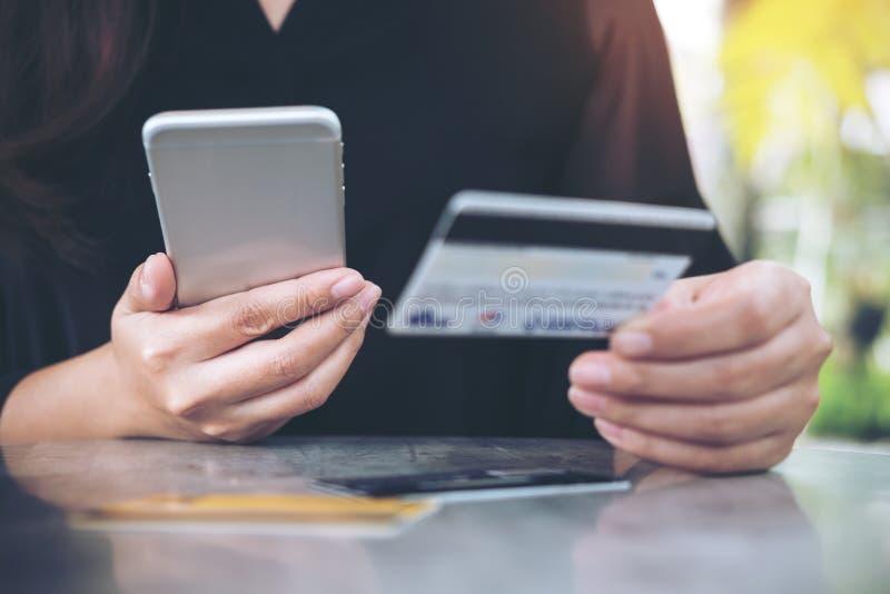 Close-upbeeld van een de holding van de vrouwen` s hand creditcard en het gebruiken van mobiele telefoon stock afbeeldingen