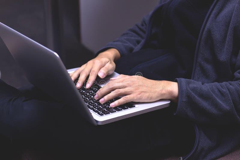 Close-upbeeld van een jonge mens die aan zijn laptop thuis werken han stock foto