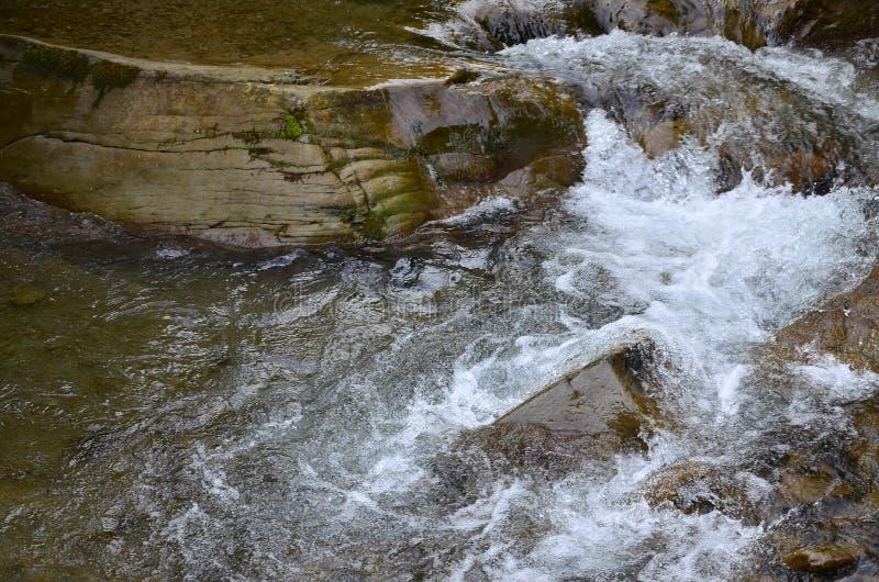 Close-upbeeld van een kleine wilde waterval in de vorm van korte stromen van water tussen bergstenen royalty-vrije stock fotografie