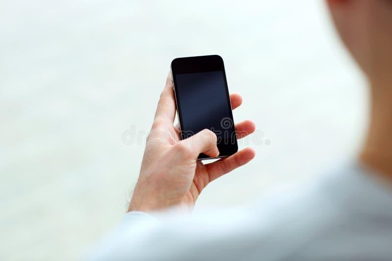 Close-upbeeld van een mensenholding smartphone en het bekijken vertoning stock foto's