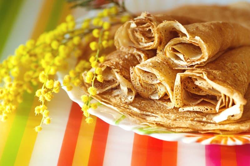 Close-upbeeld van gouden pannekoeken over kleurrijke achtergrond stock foto