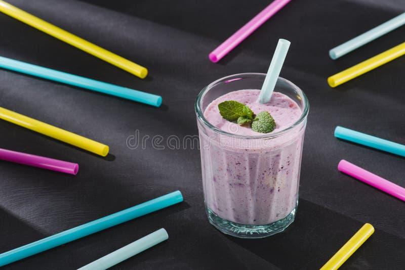 close-upbeeld van het drinken stro en glas van bes smoothie royalty-vrije stock foto's