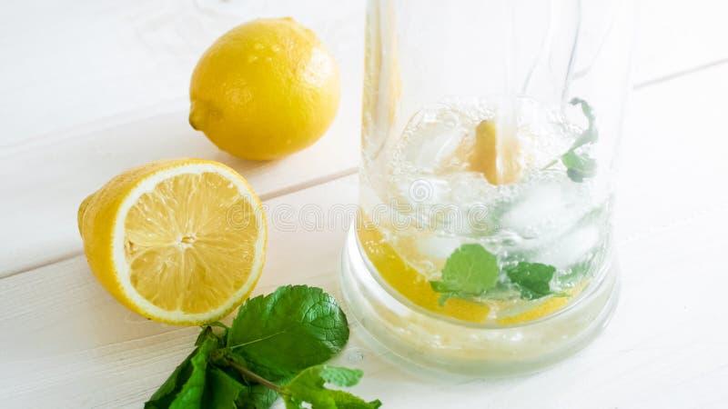 Close-upbeeld van het gieten van koud water in glas met citroenen, munt en ijs stock foto's