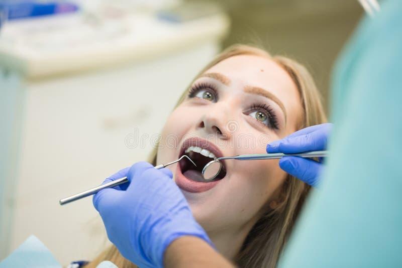 Close-upbeeld van jonge vrouwenzitting als voorzitter van de tandarts met geopende mond op het kantoor van de tandarts terwijl he royalty-vrije stock fotografie