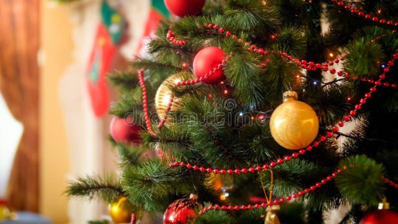 Close-upbeeld van kleurrijke lichten die op versierde Kerstboom bij huis gloeien stock afbeeldingen