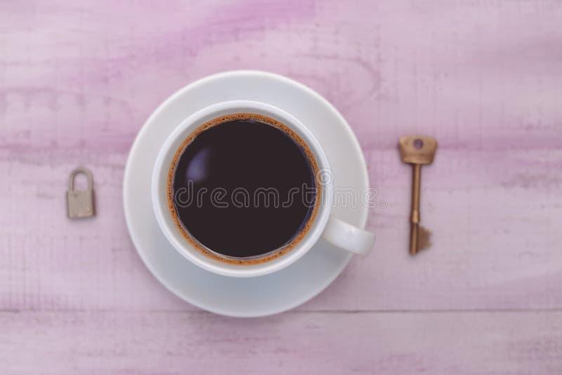 Close-upbeeld van kop van koffie met slot en sleutel stock afbeelding