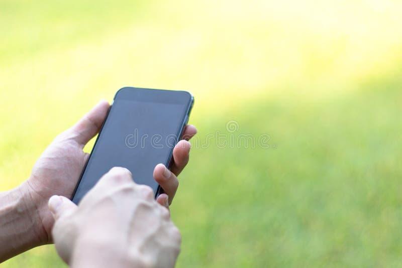 Close-upbeeld van mannelijke handen die zwarte smartphone in park, mens gebruiken stock afbeeldingen
