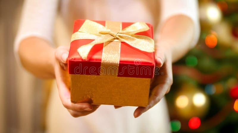 Close-upbeeld van mooie jonge vrouw die rode giftdoos met gouden lintboog houden stock fotografie