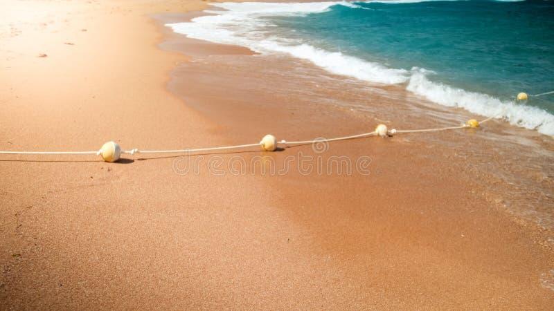 Close-upbeeld van plastic drijvende die boeien in lijn die door kabel worden verbonden op het overzeese strand liggen Perfect sch stock foto's