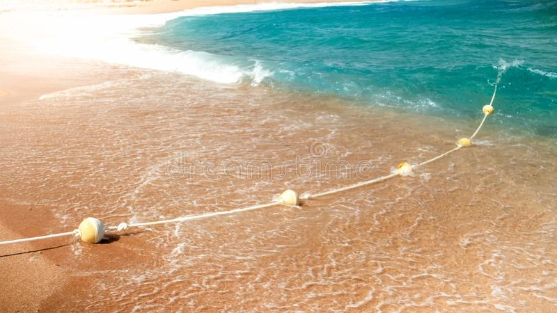 Close-upbeeld van plastic drijvende die boeien in lijn die door kabel worden verbonden op het overzeese strand liggen Perfect sch stock fotografie