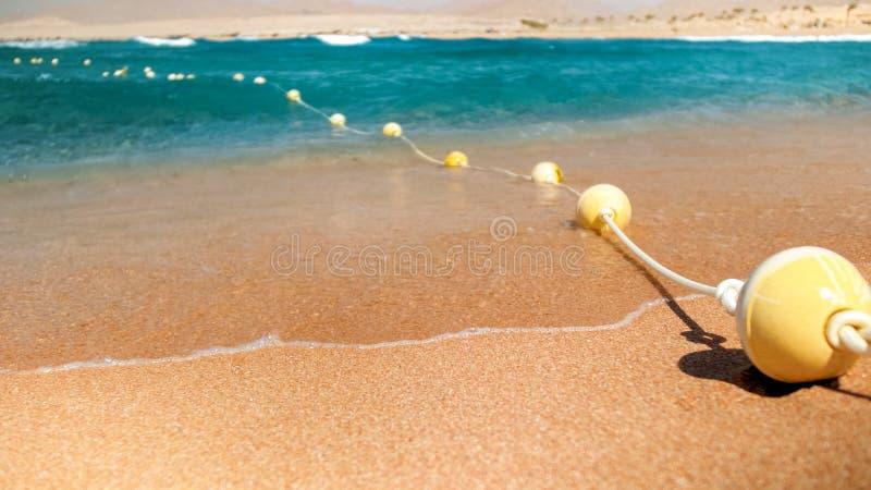 Close-upbeeld van plastic drijvende die boeien in lijn die door kabel worden verbonden op het overzeese strand liggen Perfect sch royalty-vrije stock fotografie