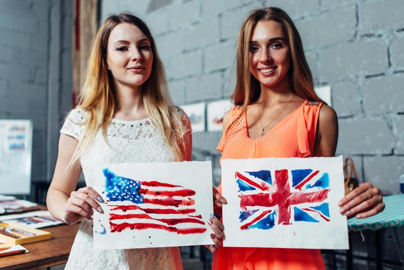 Close-upbeeld van twee jonge vrouwen die een tekening van Britse en Amerikaanse vlaggen hand-drawn met aquarelle techniek houden royalty-vrije stock foto