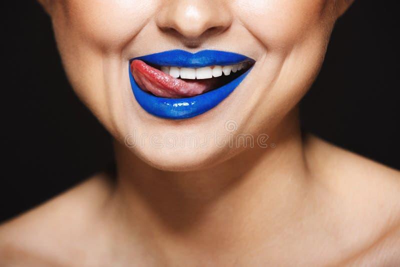 Close-upbeeld van vrolijke meisjes` s glimlach met blauwe lippenstift Tong die lippen likken royalty-vrije stock fotografie