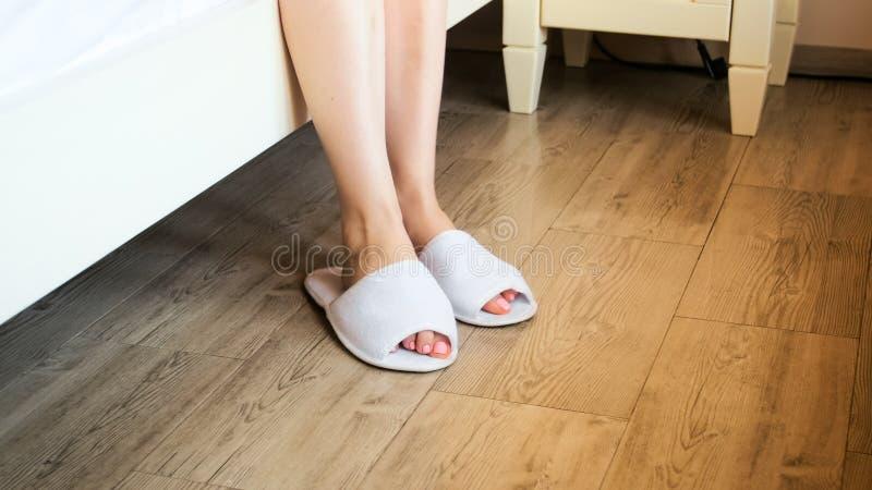 Close-upbeeld van vrouwelijke voeten die witte hotelpantoffels dragen bij bed royalty-vrije stock afbeeldingen