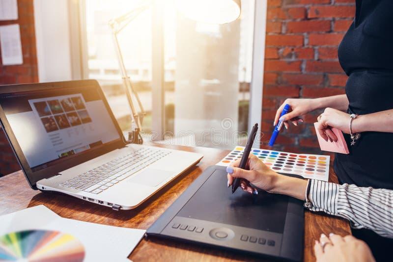 Close-upbeeld van vrouwen die een project trekken die een grafische tablet en een laptop zitting in modern bureau gebruiken stock fotografie