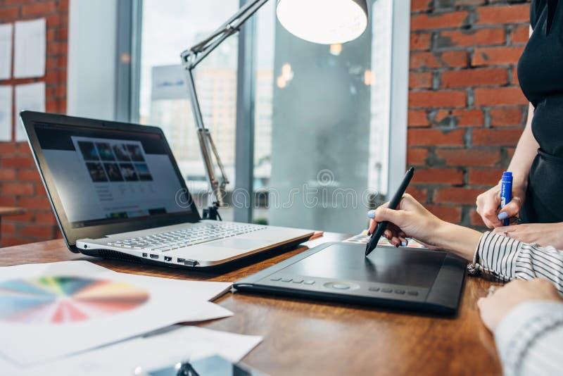 Close-upbeeld van vrouwen die een project trekken die een grafische tablet en een laptop zitting in modern bureau gebruiken royalty-vrije stock foto's