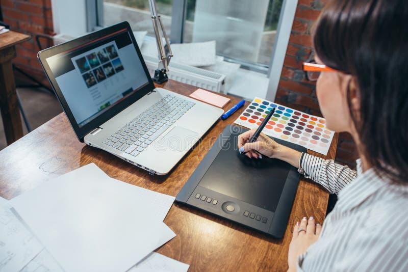 Close-upbeeld van vrouwen die een project trekken die een grafische tablet en een laptop zitting in modern bureau gebruiken stock foto's