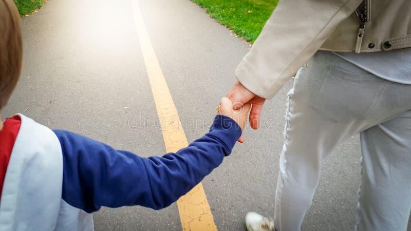 Close-upbeeld van weinig 3 van de oude peuterjaar jongen die zijn moeder houden met de hand en in park op weg lopen royalty-vrije stock fotografie
