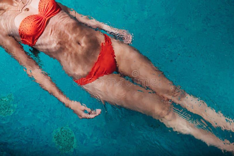 Close-upbeeld van wijfje die bikini dragen die op terug in blauw water zwemmen stock fotografie