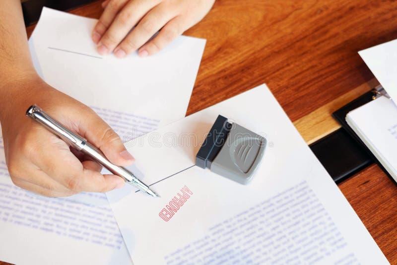 Close-upbeelden van de handen van zakenlieden die en in goedgekeurde contractvormen ondertekenen stempelen royalty-vrije stock afbeelding