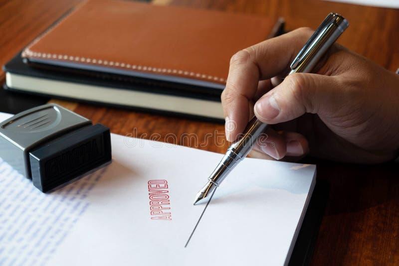 Close-upbeelden van de handen van zakenlieden die en in goedgekeurde contractvormen ondertekenen stempelen royalty-vrije stock fotografie