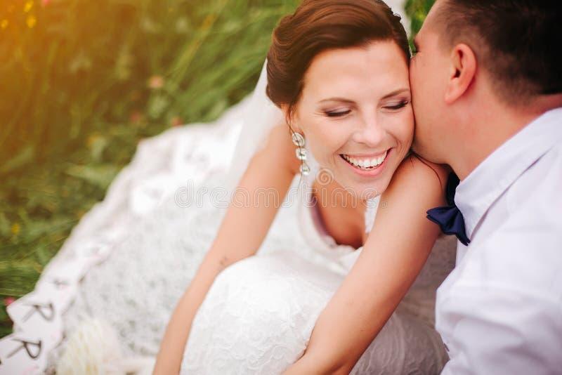 Close-upbruid die terwijl bruidegom het fluisteren complimenten aan haar glimlachen royalty-vrije stock fotografie