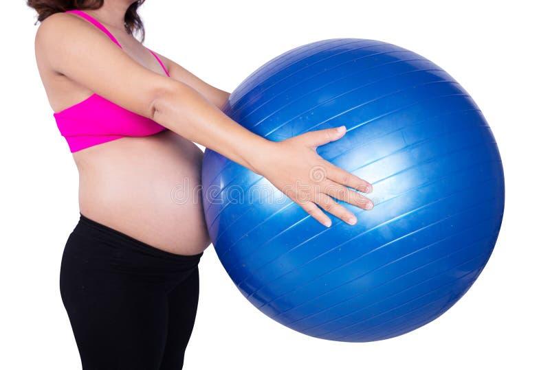Close-upbuik van Zwangere vrouw met geschiktheidsbal op witte rug stock afbeelding