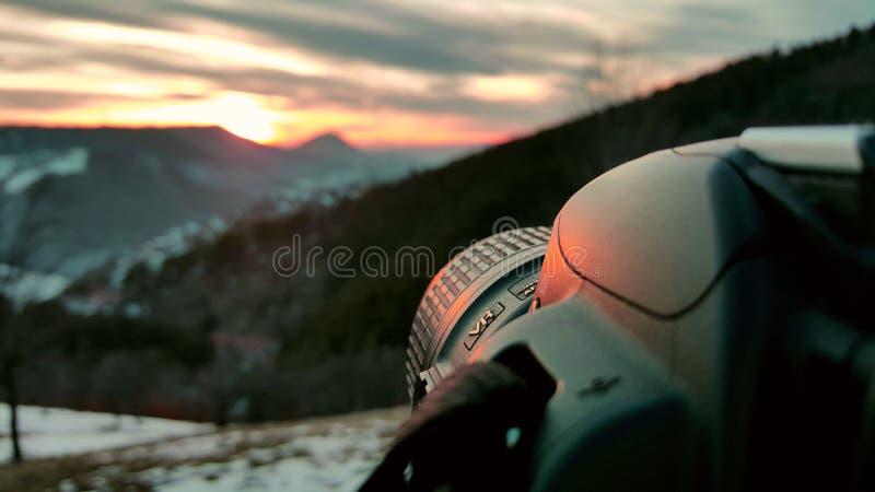 Close-upcamera wordt geplaatst om de zonsondergang te vangen die De winterlandschappen, oranje hemel en zonsondergang op de achte stock foto's