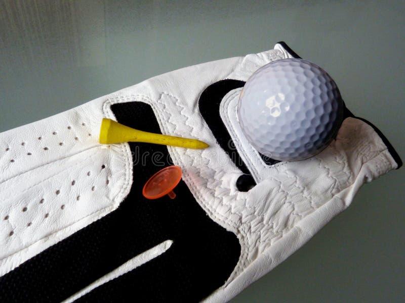 Close-updetail van de golfbal van de golfhandschoen en geel T-stuk stock foto's