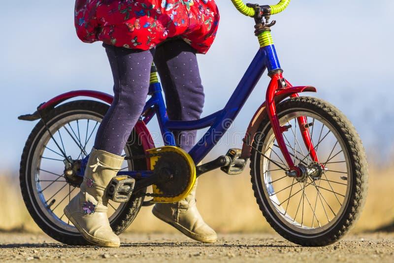 Close-updetail van de voeten van het meisjekind op een kindfiets stock foto's