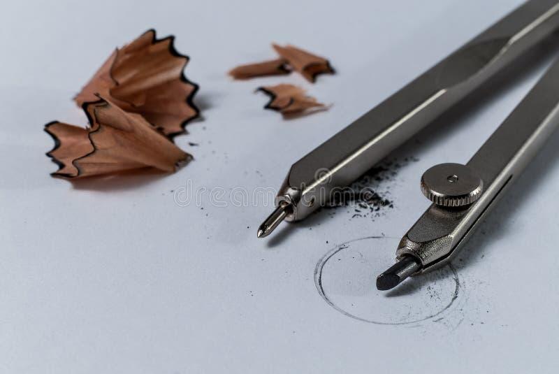 Close-updetail van een kompas van het meetkundepotlood en potlood een scherpend schaafsel op Witboek met een getrokken cirkel royalty-vrije stock foto