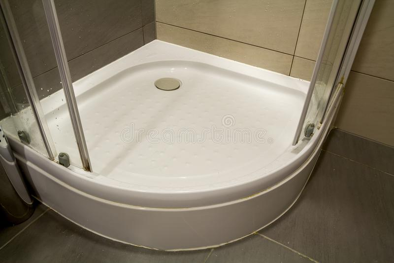 Close-updetail van nieuwe moderne schone lege witte douchecabine met dalingen van water op transparante glasdeur en aardig licht  stock afbeelding