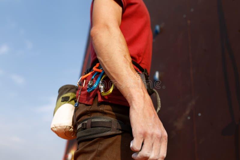 Close-updetail van rotsklimmer die veiligheidsuitrusting dragen en materiaal beklimmen openlucht dat de zak van het krijtmagnesiu stock foto's