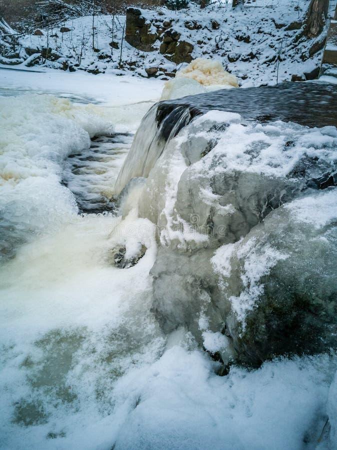 Close-updetails van Bevroren Waterval in Bewolkte de Winterdag met Sneeuw die de Grond behandelen royalty-vrije stock foto's