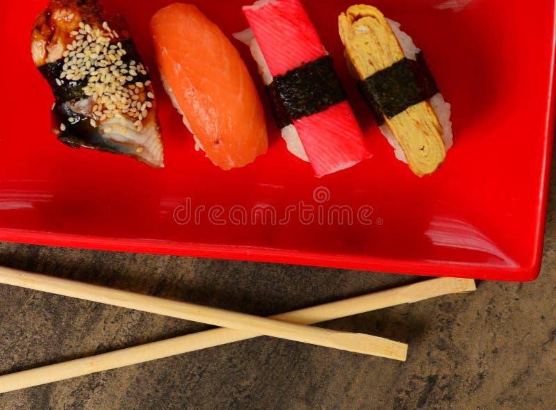 Close-upeetstokjes en rij van sushi stock afbeeldingen