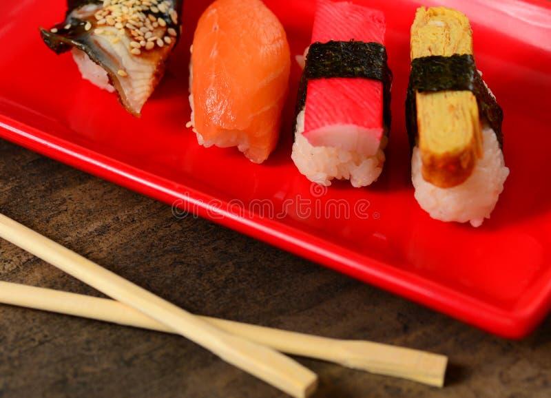 Close-upeetstokjes en rij van sushi royalty-vrije stock afbeelding