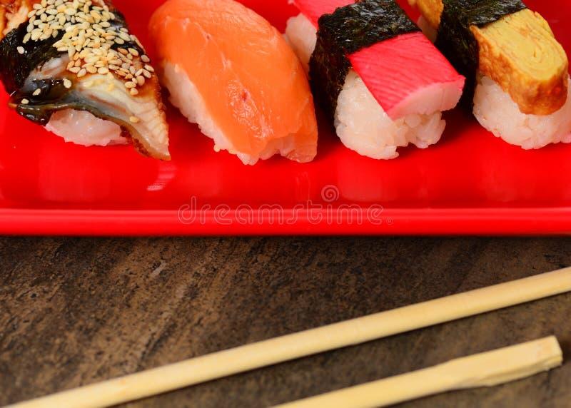 Close-upeetstokjes en rij van sushi royalty-vrije stock afbeeldingen